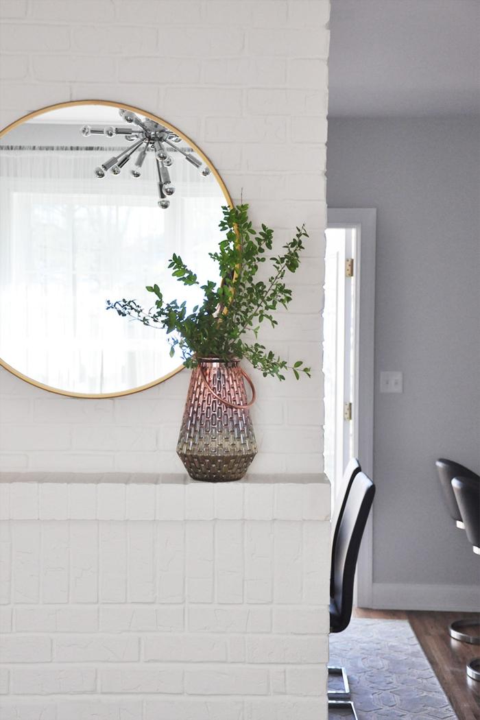 miroir décoratif rond, deco cheminee style scandinave, ambiance blanche, chaises noires