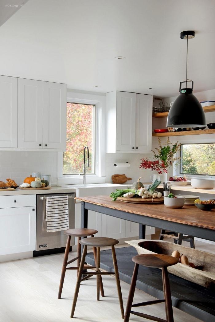 cuisine en blanc et acier de style traditionnel au coeur de la quelle règne un ilot central table industrielle en bois et métal accentuée par un luminaire suspendu d'esprit atelier