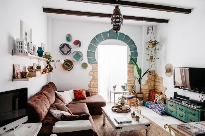 ambiance exotique avec objets décoratifs de style ethnique chic dans un salon blanc avec poutres de bois foncé sur le plafond
