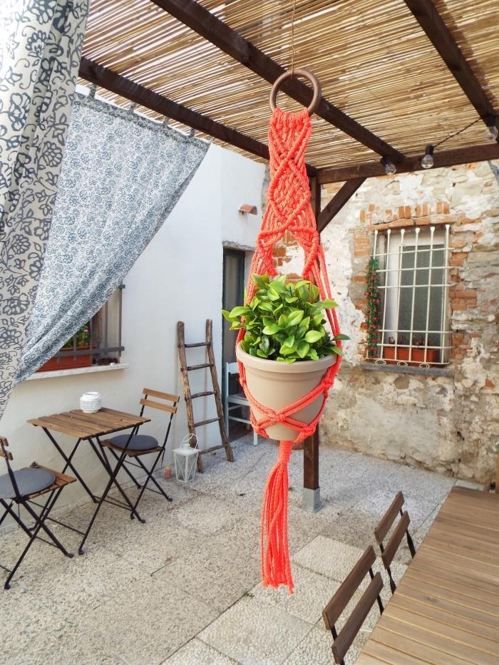 exemple comment décorer son jardin avec une suspension plante en macramé de couleur rouge, idée aménagement pergola avec meubles bois