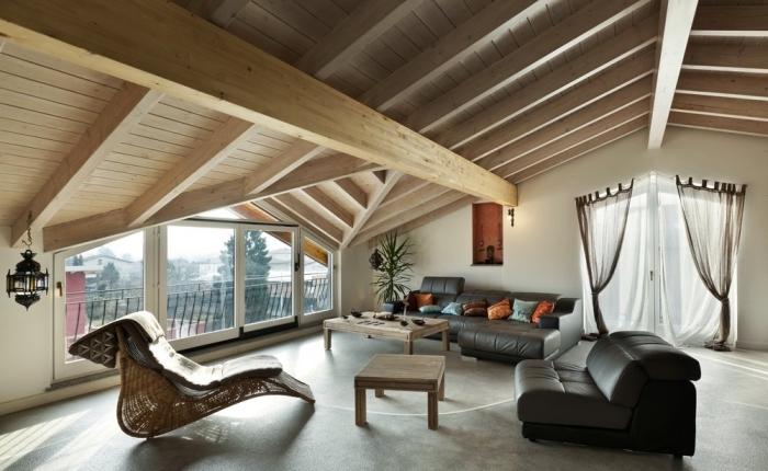 design intérieur de style moderne dans une pièce mansardée aux murs blancs avec joli plafond en poutres de bois clair
