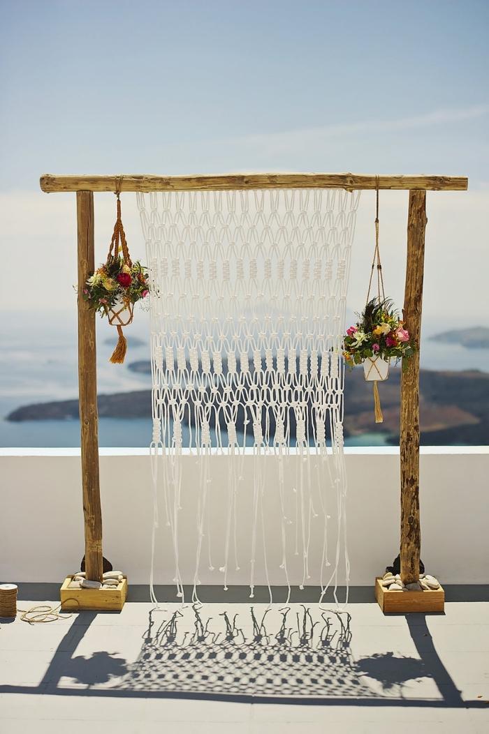 exemple de décor mariage en style boho avec un arc en bois et rideaux en macramé, modèle de suspension plante en fil rouge