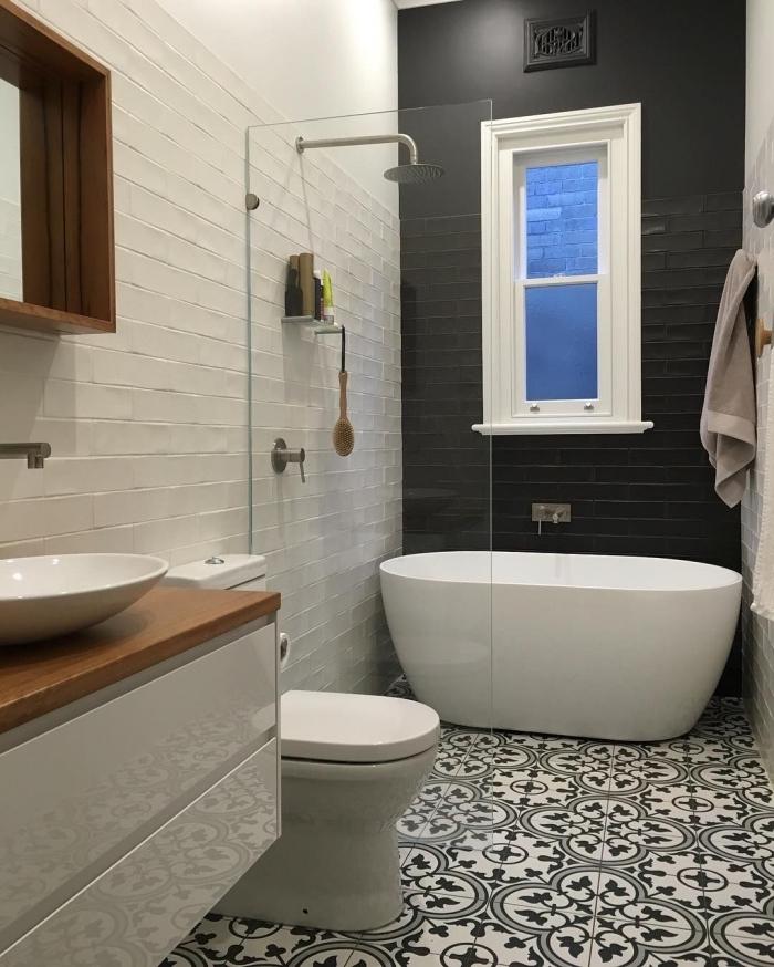 des carreaux de ciment noir et blancs à motifs arabesques de taille différente qui s'accorde avec l'ambiance élégante de la salle de bain noir et blanc qui joue sur l'effet brillant et mat de ses murs et ses meubles