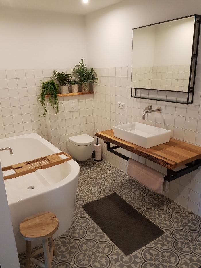 une salle de bain carreaux de ciment à larges motifs arabesques qui dynamise l'ambiance épurée de cette salle de bain avec baignoire aux accents industriels