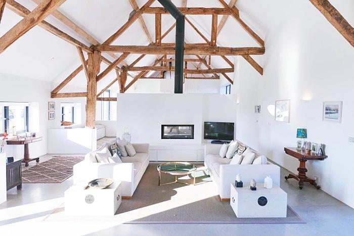 exemple aménagement studio chaleureux en blanc avec poutres de bois sur les murs et le plafond, idée déco salon cozy
