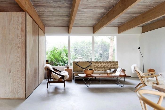 idée déco avec poutre apparente dans un salon scandinave aménagé dans style minimaliste avec coussins et plaids à textures ethniques