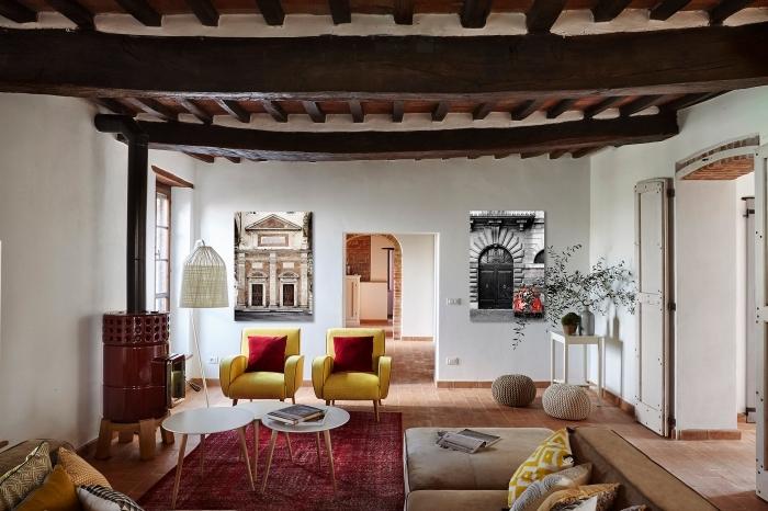 intérieur à design ethnique chic avec coussins aux motifs traditionnels et meubles de bois et cuir, exemple de plafond rustique ou campagnard avec poutres bois foncé