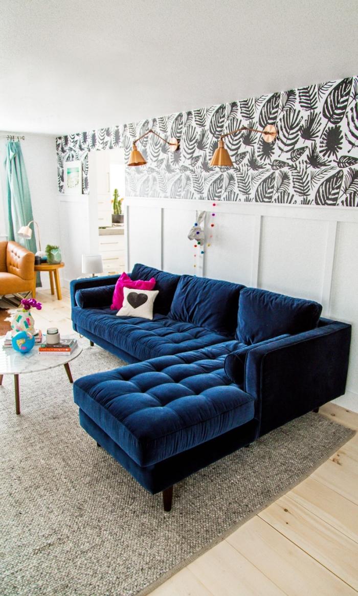 salon vintage chic aux accents colorés avec une frise papier peint à motif végétal noir et blanc posé en haut du mur, au-dessus du lambris peint blanc