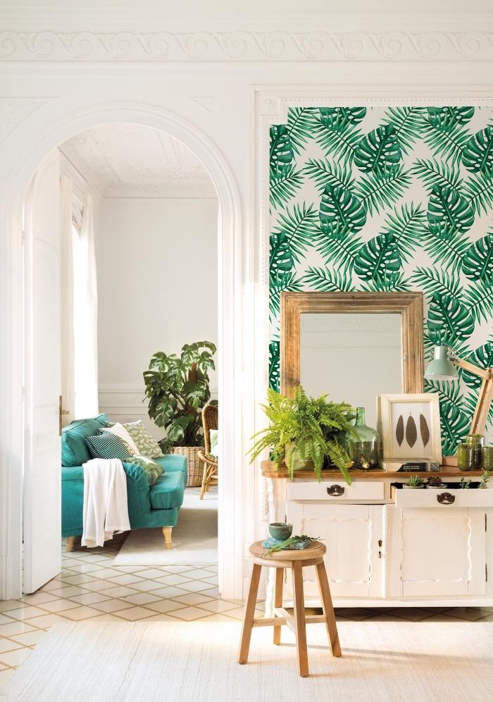 du papier peint tendance 2018 à motif tropical feuilles de palmier posé sur un pan de mur, derrière la commode d'esprit campagne chic façon un panneau décoratif