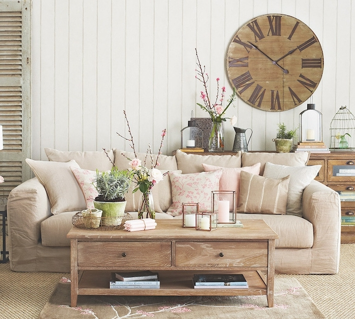 exemple de deco campagne avec canapé beige, table basse bois, lambris blanc, horloge vintage, vases de fleurs, objets anciens