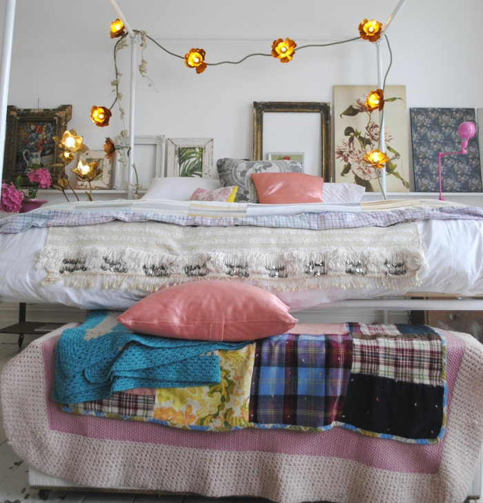 peintures encadrées, guirlande lumineuse, coussins roses, chambre à deco romantique