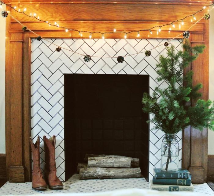 décor rustique créé avec bottes de jardin, une fausse cheminée décorative, branche de pin et bûches