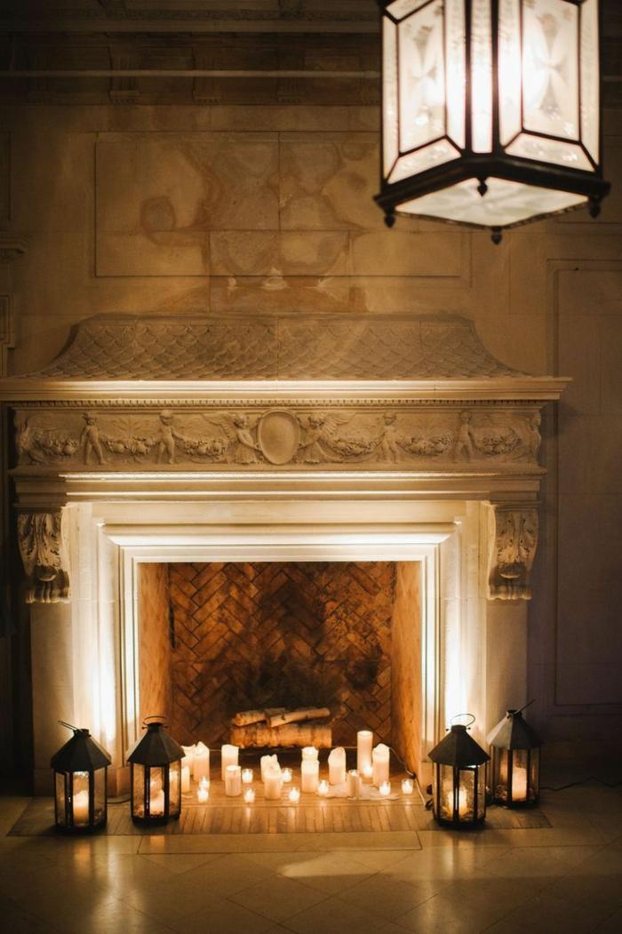 lanterne orientale suspendue au-dessus d'une cheminée murale blanche décorée de bougies blanches