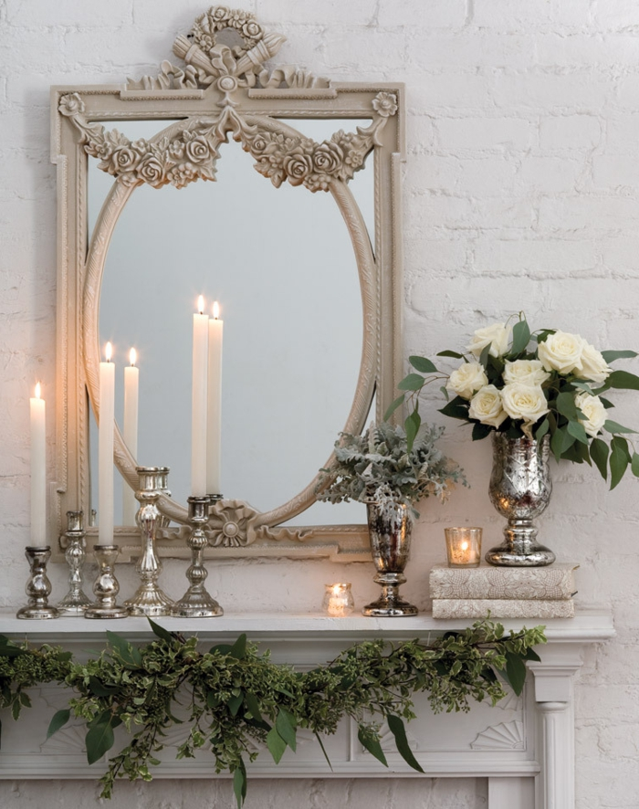 miroir antique, bougies blanches et bougeoirs métalliques, vase argentée avec roses blanches,
