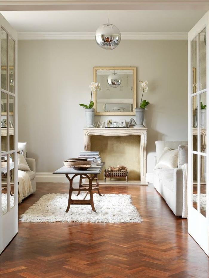 tapis blanc, table basse, lampe argentée, sol chevron foncé, miroir encadré de bois, deco cheminee