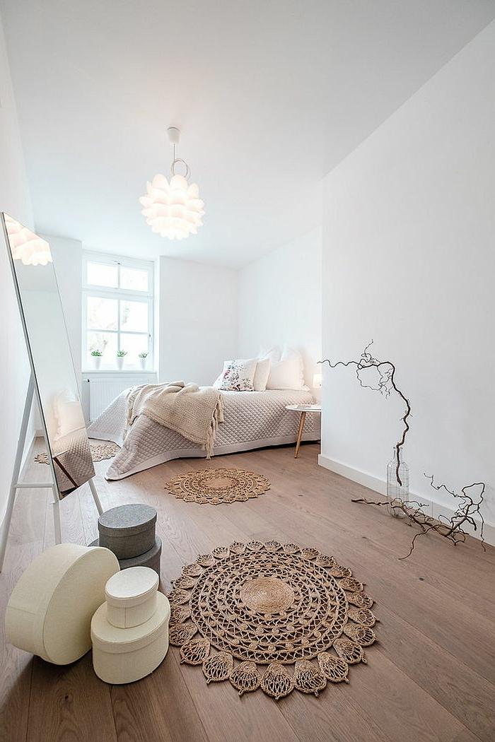 sol en planches de bois, tapis macramé, grand miroir rectangulaire, peinture murale blanche, aménagement chambre