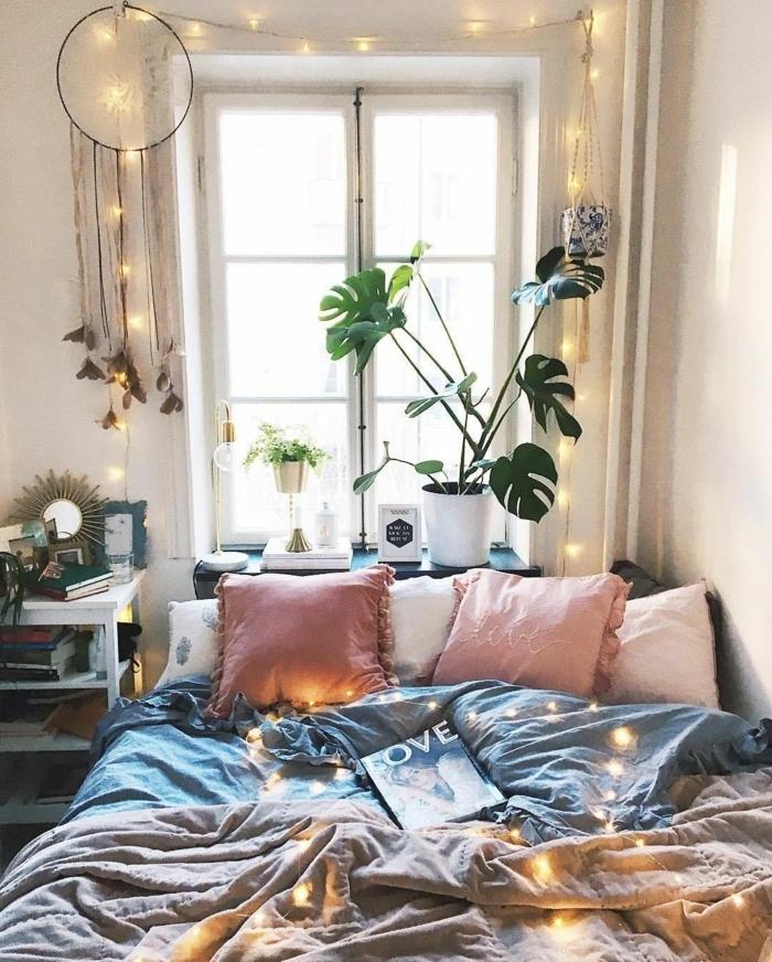 joli aménagement chambre, coussins roses, literie grise, pot de fleurs blanc avec plante verte, fenêtre, attrape-rêves, guirlande lumineuse