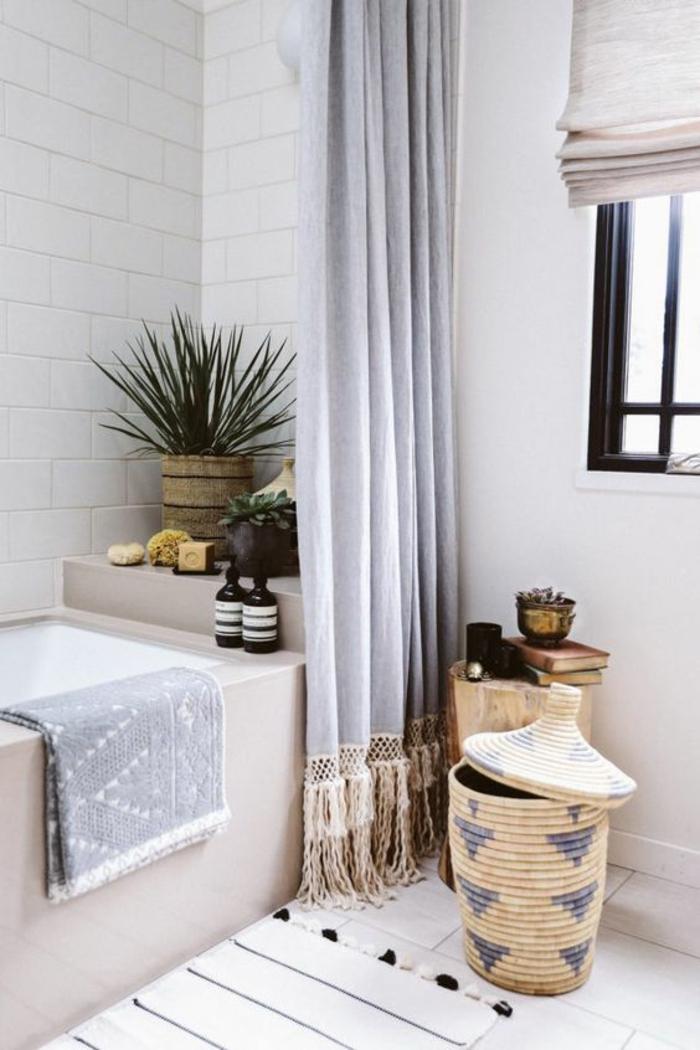 salle de bain 4m2, arrelage blanc, baignoire rectangulaire en couleur ivoire, panier en paille tressée en beige et bleu marine, rideaux gris avec des franges beiges