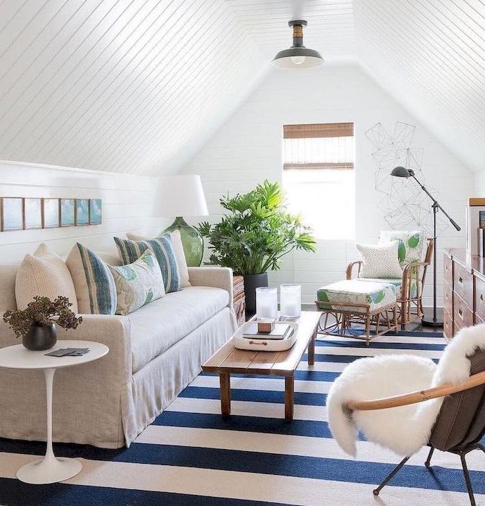 eco salon cosy sous pente style campagne, chaise longue bois, canapé gris, tapis rayures bleue t blanc, table basse bois rustique, murs blancs