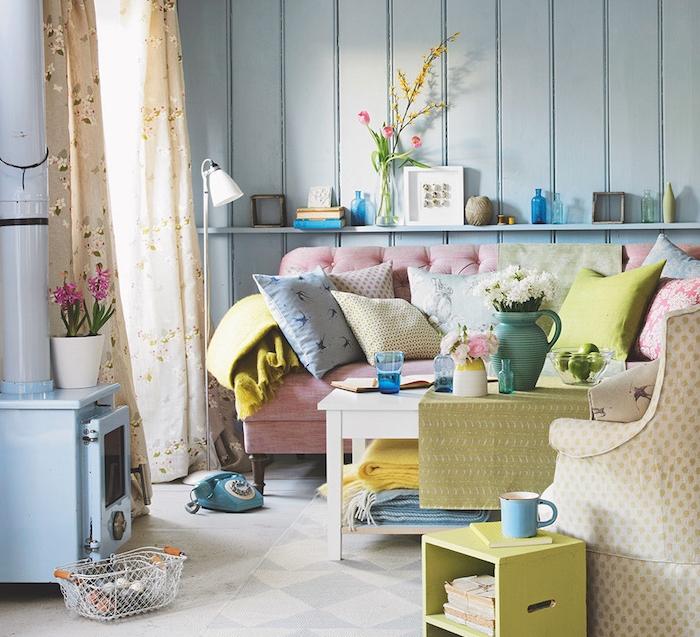 salon chaleureux deco de charme, lamris bleu, canapé rose poudré, coussins décoratifs colorés, table basse blanche, fauteuil beige, rideaux fleuris