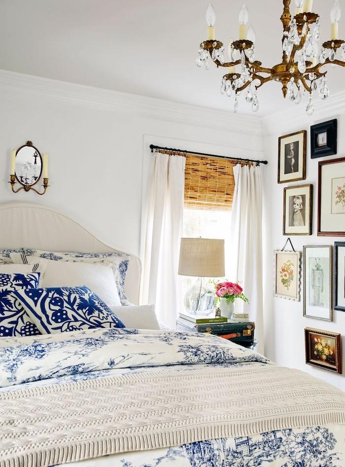 deco de charme dans une chambre style campagne linge de lit bleue t blanc, mur peinture blanche, lustre élégant, deco murale de cadres dessins et photos noir et blanc, table de nuit en malle vintage