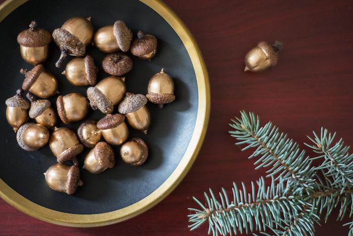 que faire avec des glans, deco glands repeints de couleur or dans une assiette noire à bordure or et branches de pin