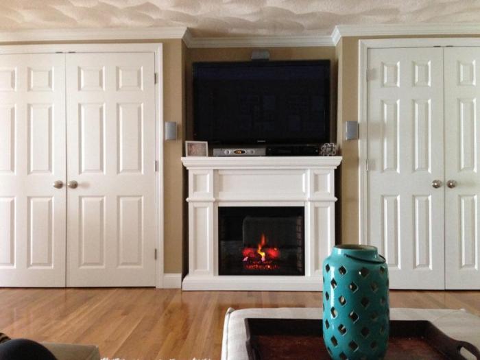 lanterne bleue, cheminée blanche aux flammes artificielles, manteau de cheminée blanc