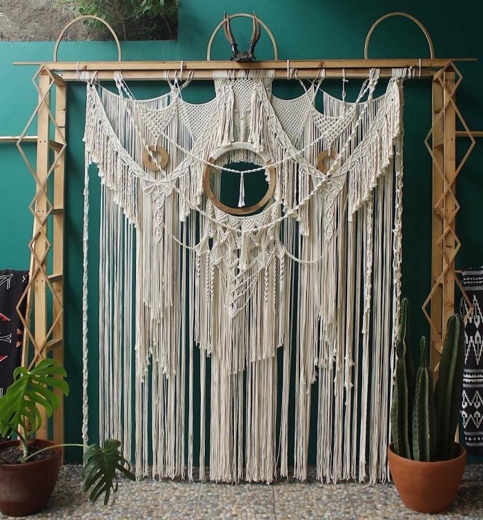 décor de style traditionnel dans un salon en peinture bleu avec plantes vertes et arc DIY en bois et rideau macramé
