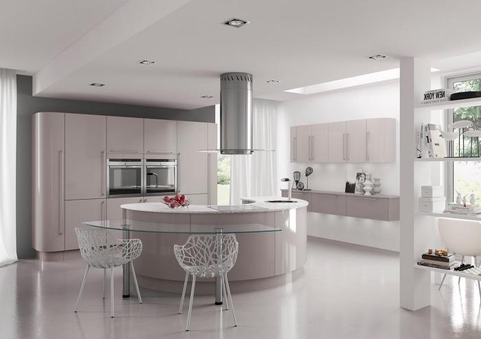 cuisine gris et rose beige moderne éclatante de lumière au centre de laquelle règne un ilot de cuisine arrondi avec coin repas en verre