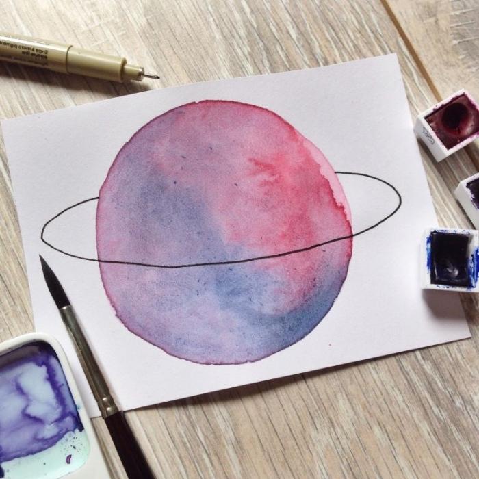 jolie planète rose-violet à l'aquarelle avec son anneau réalisé au feutre noir, peinture facile pour apprendre l'aquarelle