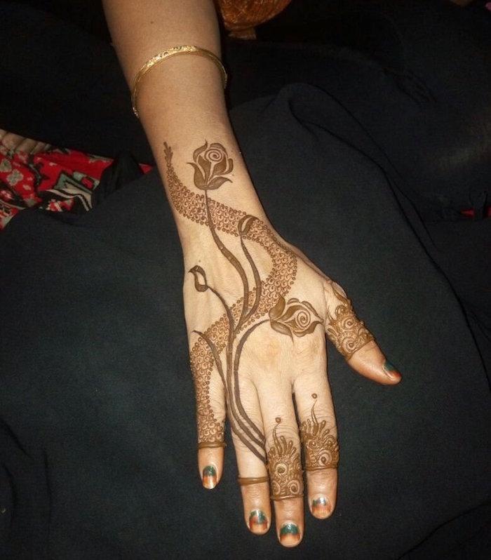 modèle dessin au henné marron avec fleurs roses sur main et poignet