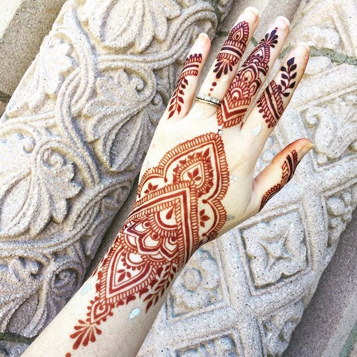 dessin sur main au henne marron après séchage avec mandala sur la poignet