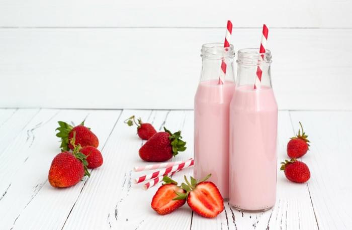 deux bouteilles de milkshake rose, fraises, paille rouge et blanche, planches blanches