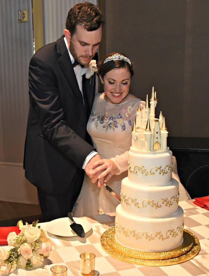 Image de gateau wedding cake château, mariage sujet Disney chateau magnifique, gateau mariage simple blanc et doré, les mariés qui coupent un morceau