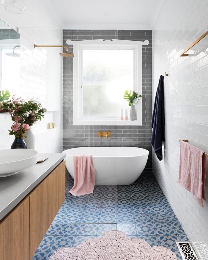 le carrelage aspect carreaux de ciment à motifs marguerites bleues de cette salle de bains moderne est associé avec des carreaux de métro blancs et gris
