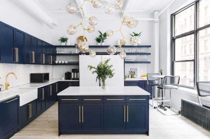 plant de travail ilot cuisine en blanc quartz associé au bleu des armoires, cuisine bleu marine aux accents en verre et or