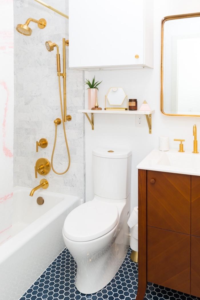 design intérieur moderne dans une petite salle de bain blanche au carrelage de sol bleu marine avec baignoire douche