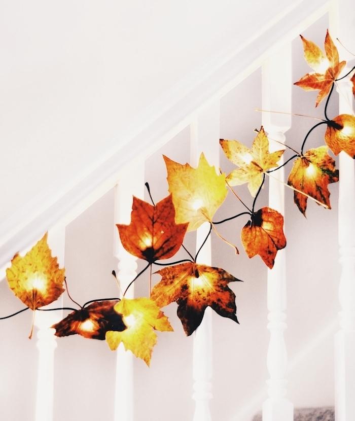 idée de deco montée escalier blanc avec des feuilles mortes accrochées sur guirlande lumineuse