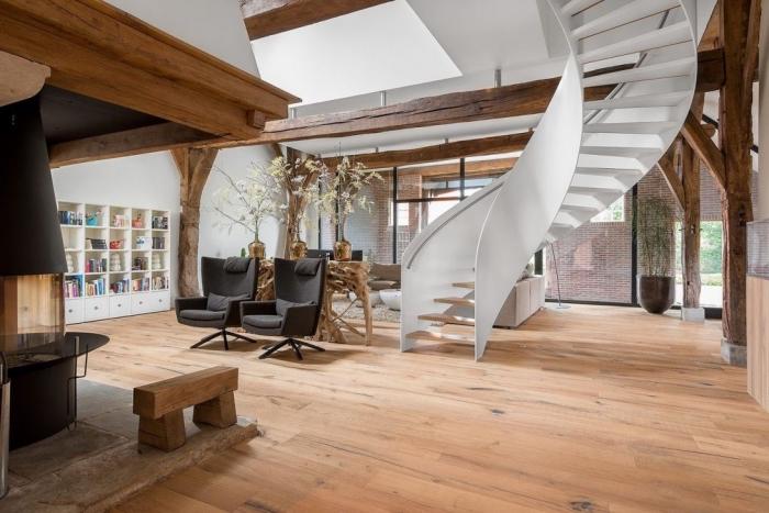 design intérieur de style contemporain dans une maison spacieuse au parquet de bois et murs blancs avec charpente apparente