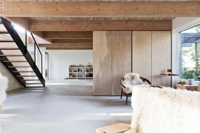 exemple de design intérieur de style scandinave dans une maison spacieuse aménagée avec meubles de bois et textures naturelles, modèle déco avec poutre en bois