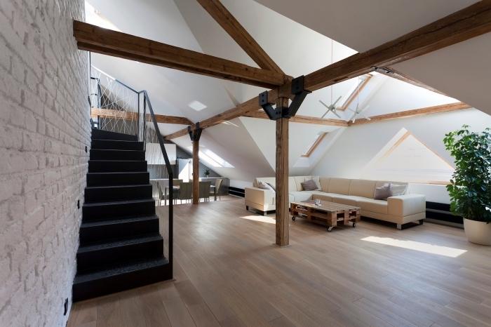 intérieur moderne dans un appartement mansardé aux murs blancs avec poutres en bois exposées sur les murs et le plafond
