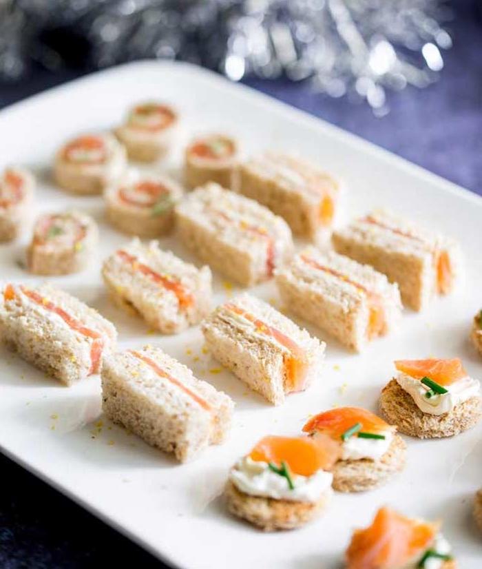 sandwich pain complet tartiné de creme fraîche épaisse, saumon fumé et herbes fraiches dans une assiette plateau de service blanc
