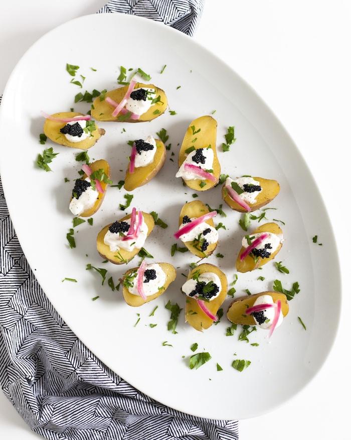 idée pour apero dinatoire raffiné avec des patates au four avec de la creme fraiche et du caviar, oignons et herbes fraiches