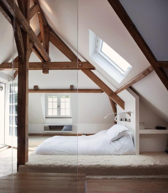 modèle de chambre à coucher aménagée dans l'esprit scandinave aux murs blancs avec charpente apparente de bois foncé