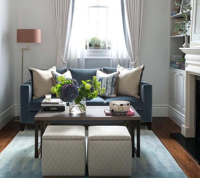 canapé bleu foncé, table basse bois et metal, tabourets originaux, tapis bleu, cheminée, deco bouquet de fleurs