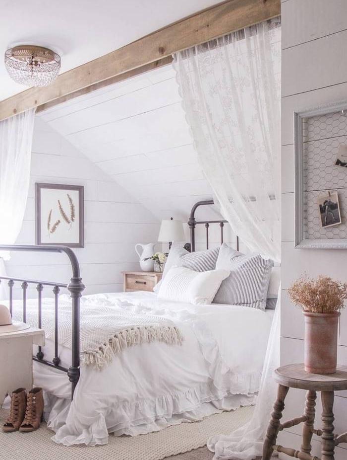 deco chambre sous pente avec poutre bois apparente, lit metallique vintage, linge de lit blanc, tapis beige, rideaux dentelle