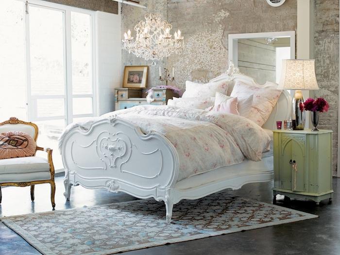 mur défraichi, lit vintage chic blanc, parure de lit motifs fleuris, tapis floral, sol gris foncé, chaise vintage, lustre élégant