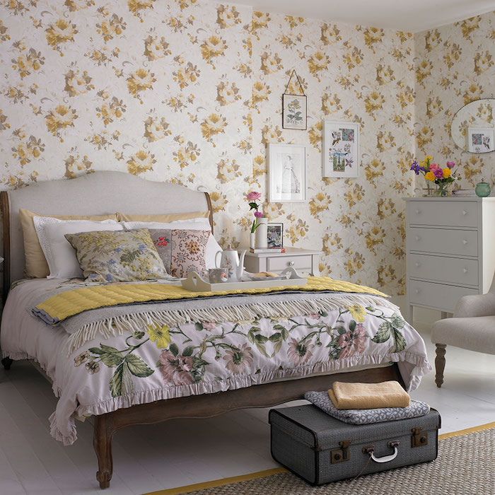 papier peint fleuri dans une chambre deco shabby, linge de lit fleuri, commode gris clair, bout de lit en malle vintage grise, parquet blanchi