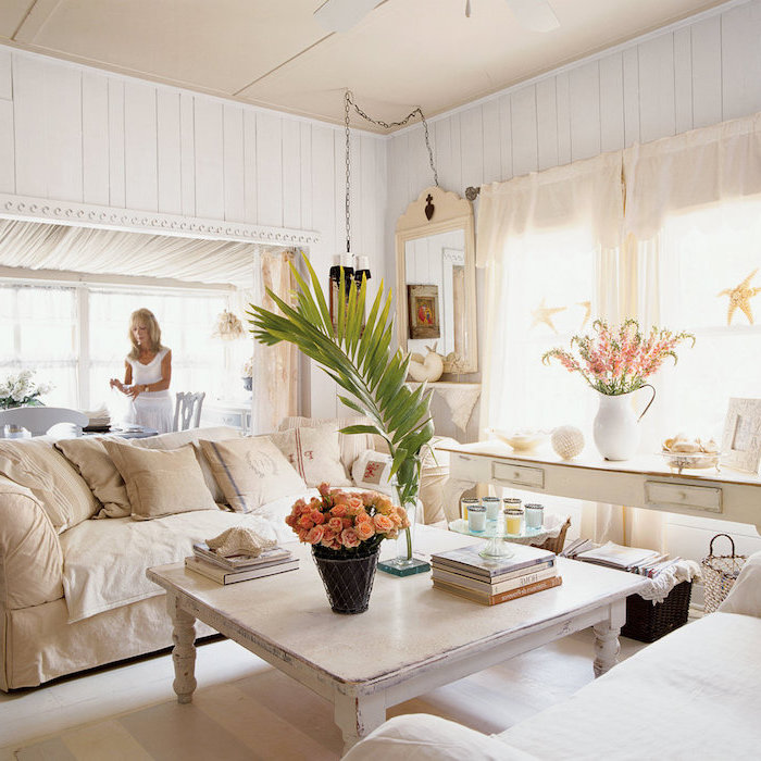 canapé beige, table basse bois patiné, canapé blanc, console decorative blanche, bouquet de fleurs, mur lambris blanc