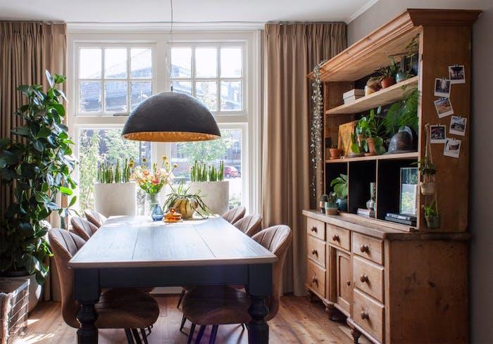 vaisselier en bois, table diner bois et chaises en metal et cuir, parquet marron, rideaux marron clair, suspension originale